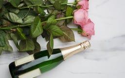 花束rpink玫瑰顶视图,在绿色瓶的香槟在白色桌上 喜事的庆祝 免版税库存图片