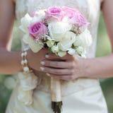 花柔和的婚礼花束在手新娘的 免版税库存照片
