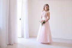 花桃红色婚礼礼服和花束的新娘  免版税图库摄影