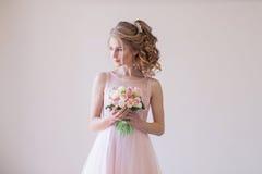 花桃红色婚礼礼服和花束的新娘  库存照片