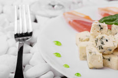 花梢午餐的特写镜头 有一把叉子的一块板材在白色向背景扔石头 红色熏火腿、绿色蓬蒿和青纹干酪 免版税库存图片