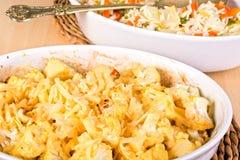 花椰菜在一个白色砂锅烘烤了洒与乳酪 免版税图库摄影