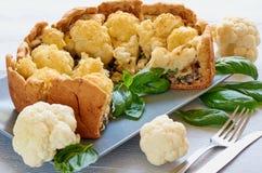 花椰菜饼健康片断在灰色板材的在明亮的厨房背景 素食主义者被切的花椰菜馅饼 免版税库存图片