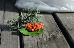 花楸浆果和婚戒在葡萄酒木板 免版税库存图片
