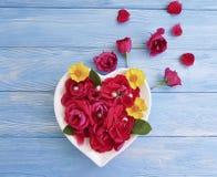 花玫瑰的心脏的板材成串珠状在蓝色木背景的装饰 免版税库存图片