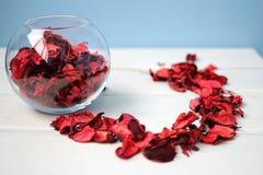 花瓶在白色桌上的玫瑰花瓣 免版税库存图片