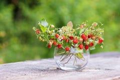 花瓶用在木桌上的草莓 免版税图库摄影