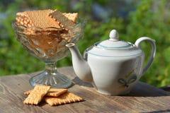 花瓶用曲奇饼和茶壶在庭院里 免版税库存图片