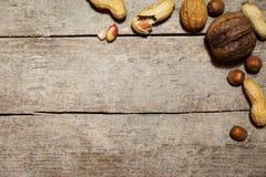 花生、核桃和榛子在木桌上 免版税库存图片