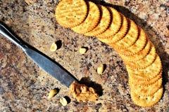 花生酱刀子和薄脆饼干 免版税库存图片