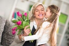 给花的女孩他的妈妈在母亲节 免版税库存照片