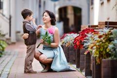 给花的小男孩他的妈妈 免版税库存照片