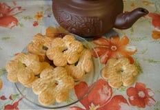 以花的形式曲奇饼在透明茶碟和棕色黏土茶壶在桌布与橙色和红色花 免版税库存图片