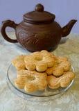 以花的形式曲奇饼在透明茶碟和棕色黏土茶壶在桌布与白玫瑰 免版税库存照片