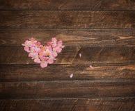 从花的葡萄酒心脏在木桌上 减速火箭的被称呼的瓦伦蒂 免版税库存照片