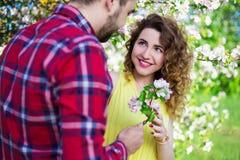 给花的年轻人愉快的女朋友在庭院里 免版税图库摄影