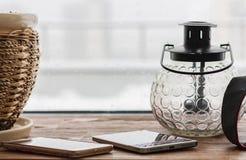 花盆、智能手机和一个烛台灯笼在一块木窗口基石,下雨天 免版税库存图片