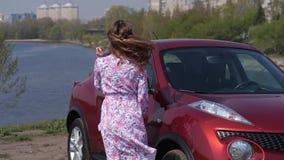花礼服的一个女孩沿汽车、神色入框架,微笑和旋转走 r 股票视频