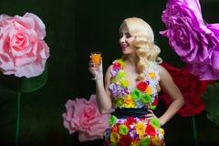花礼服的美丽的妇女在大花背景的  库存照片