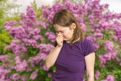 花粉过敏概念 少妇打喷嚏 开花的树在背景中 库存图片