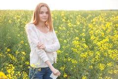 花粉过敏,打喷嚏在花的油菜籽领域的女孩 免版税库存照片