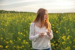 花粉过敏,打喷嚏在花的油菜籽领域的女孩 图库摄影