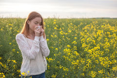 花粉过敏,打喷嚏在花的领域的女孩 免版税图库摄影