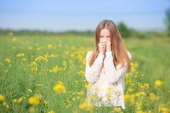 花粉过敏,打喷嚏在花的领域的女孩 免版税库存图片