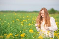 花粉过敏,打喷嚏在花的领域的女孩 免版税库存照片