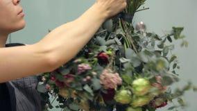 花编排者包裹圆的花束与一条深绿丝带 股票录像
