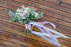 花美丽的婚礼花束在木地板上的 免版税库存图片
