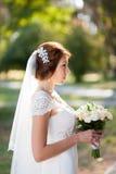 花美丽的婚礼花束在年轻新娘的手上 免版税库存图片