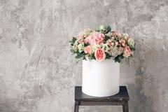 花美丽的嫩花束在白色箱子的在与空间的灰色ackground文本的 库存照片