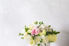 花美丽的嫩花束在白色箱子的在与空间的轻的ackground文本的 免版税库存图片