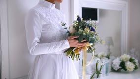 花美丽的花束在年轻新娘的手上在白色婚礼礼服穿戴了 股票录像