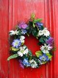 花花圈在红色门的 库存照片