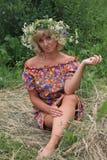 花花圈的女孩在饲槽 图库摄影