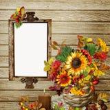 花花束、叶子和莓果在一个柳条花瓶,照片框架或者文本在木背景 免版税库存图片