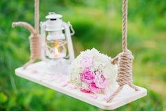 花花束与一盏煤油灯的在摇摆在森林里 库存图片