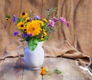 花花束在一个白色花瓶的在一张木桌上 库存照片