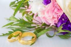 花花束在婚礼之日、新娘和新郎的爱、圆环和五颜六色的花花束  免版税库存图片