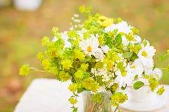 花花束在桌上的与白色桌布 库存照片