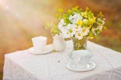 花花束在桌上的与白色桌布 免版税库存图片