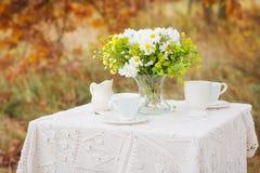 花花束在桌上的与白色桌布 免版税库存照片