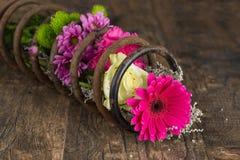 花花束在金属春天在难看的东西木表面艺术家 免版税库存图片