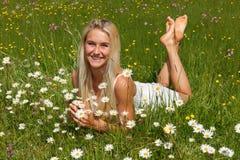 花草甸的愉快的少妇 免版税库存照片