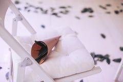 花装饰花束在一把木折叠椅的在白色 免版税库存照片