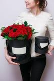 花豪华花束在帽子箱子的 在手妇女的玫瑰 红色和黑颜色 免版税库存图片