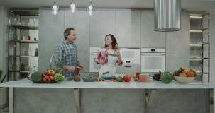 花费一对成熟夫妇的滑稽的时间在dacing现代的厨房里,当做食物时 股票录像