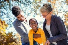 花费与他们的女儿的年轻混合的族种夫妇时间 免版税库存照片
